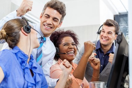 Photo pour Représentants du service clientèle gaie et gestionnaire célébrant le succès au guichet au bureau - image libre de droit