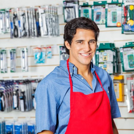 Photo for Portrait of handsome young worker in red apron smiling at hardware shop - Royalty Free Image