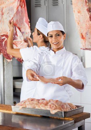 Female Butcher Offering Raw Meat At Shop