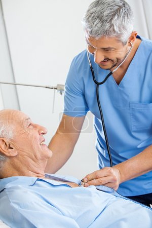 Photo for Smiling male caretaker examining senior man with stethoscope in bedroom at nursing home - Royalty Free Image