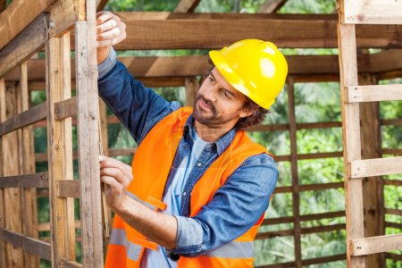 Construction Worker Measuring Timber Frame