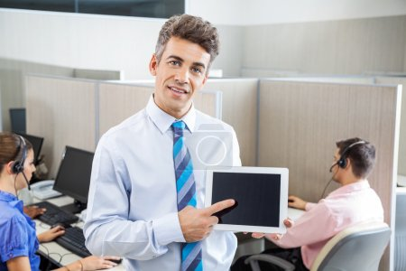 Manager Pointing At Tablet Computer In Call Center