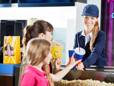 Sisters Buying Snacks From Concession Worker At Cinema