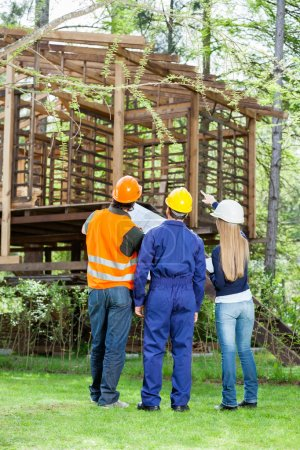 Architects Discussing Over Incomplete Timber Cabin At Site
