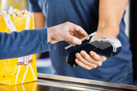 Man Making Payment Through NFC Technology At Cinema