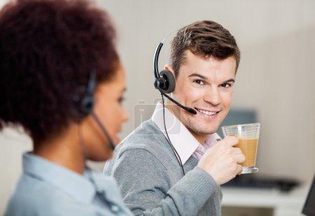 Customer Service Representative Having Tea In Office