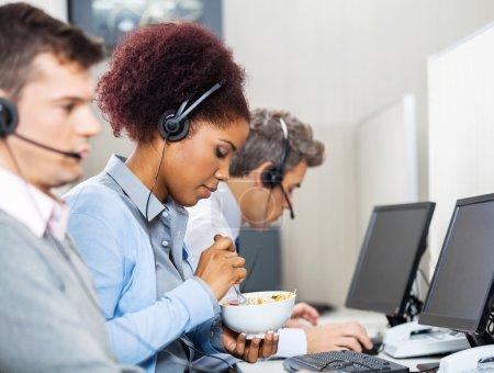 Female Customer Service Representative Having Food In Office