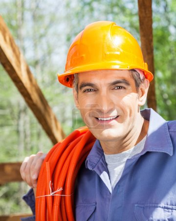 Smiling Construction Worker Carrying Rolled Pipe At Site
