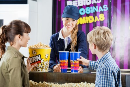 Brother and sister buying popcorn from female sell...