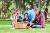 Famiglia che gode di pic-nic al campeggio