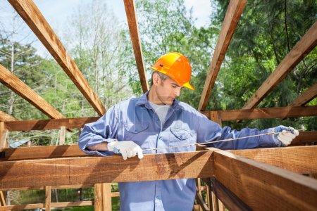 Construction Worker Measuring Timber Frame