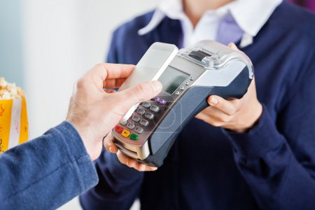 Man Using NFC Technology To Pay Bill At Cinema
