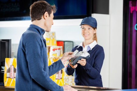 Female worker accepting payment from man through N...