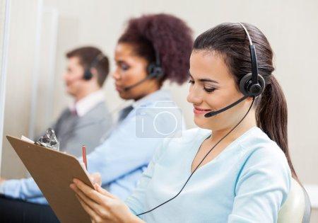 Customer Service Representative Writing On Clipboard In Office