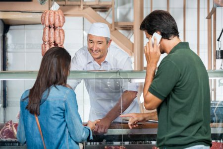 Butcher Selling Meat To Couple In Butchery