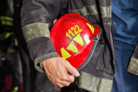 Firefighter Holding Red Helmet At Fire Station
