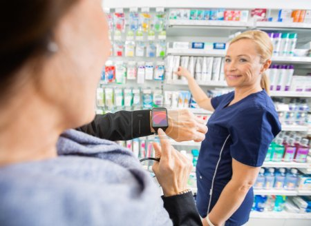 Customer Showing Smartwatch To Mature Pharmacist