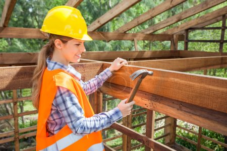 Smiling Female Worker Hammering Nail On Timber Frame