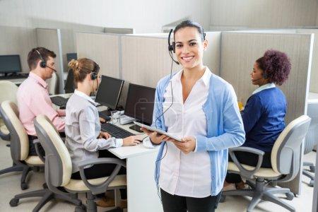 Foto de Retrato de feliz femenina representante sostiene tablet PC mientras sus colegas trabajando en segundo plano en el centro de llamadas - Imagen libre de derechos