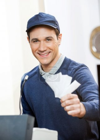 Smiling Worker Holding Tickets At Box Office