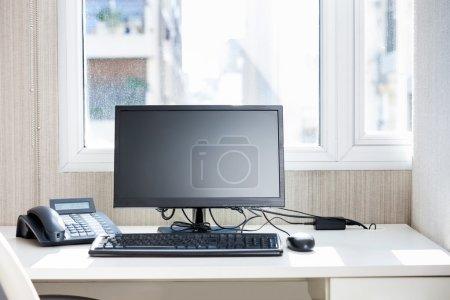 Computer And Landline Phone On Desk