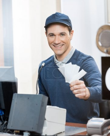Worker Holding Tickets At Box Office Counter