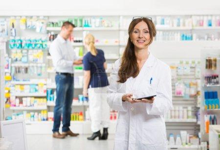 Smiling Female Chemist Holding Digital Tablet At Pharmacy