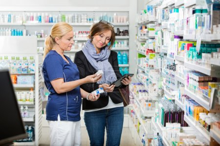 Chemist Holding Eye Drops While Customer Using Digital Tablet