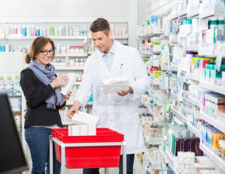 Male Chemist Showing Medicines To Female Customer