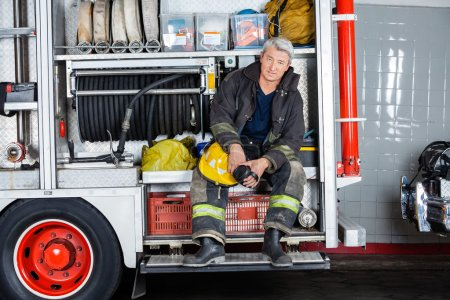 Confident Fireman Sitting In Truck At Fire Station