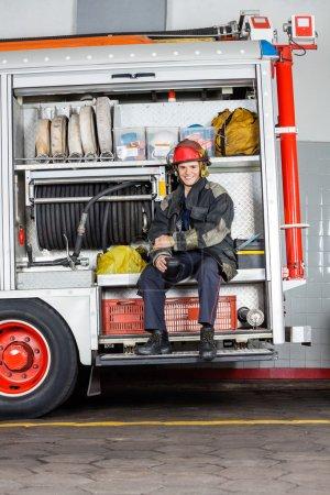 Happy Fireman Holding Coffee Mug In Truck