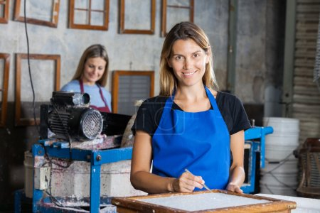 Confident Female Worker Using Tweezers To Clean Paper On Mold