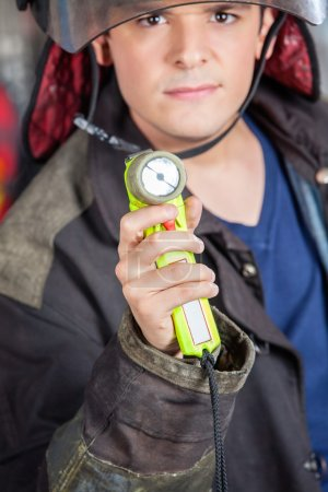 Confident Fireman Holding Torch At Fire Station