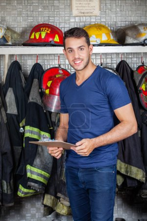 Smiling Firefighter Holding Clipboard At Fire Station