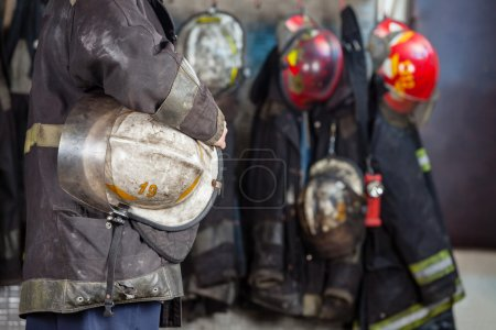 Worker Holding Helmet At Fire Station