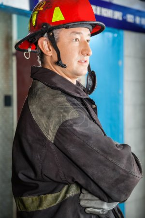 Side View Of Confident Firefighter At Fire Station
