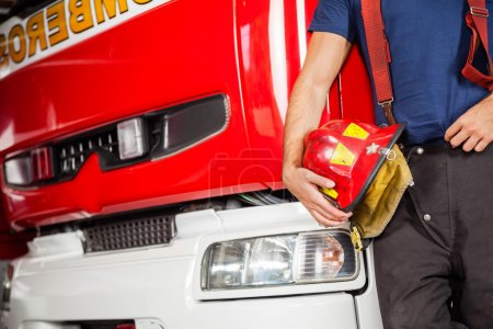 Photo for Midsection of male firefighter holding red helmet while leaning on firetruck at station - Royalty Free Image