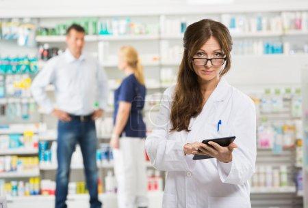 Female Chemist Holding Digital Tablet At Pharmacy