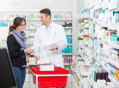 Photo for Smiling male pharmacist showing medicines to female customer in pharmacy - Royalty Free Image
