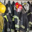 Firefighter suits and helmets hanging at fire stat...