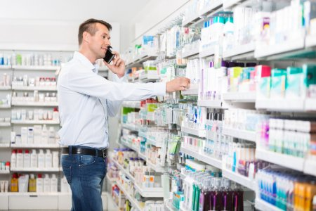 Man Using Mobile Phone While Selecting Product In Pharmacy