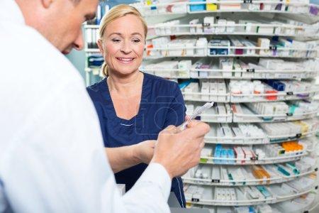 Pharmacist Explaining Product Details To Customer