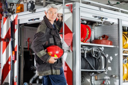 Confident Fireman Standing On Fire Engine