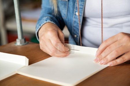 Closeup Of Worker Inserting Needle In Paper