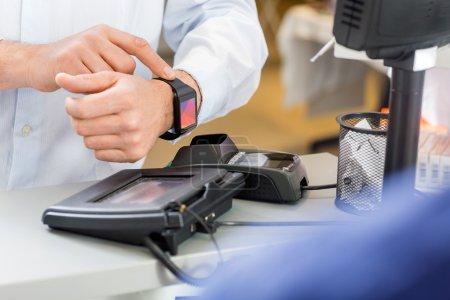 Photo pour Gros plan du client masculin payant par smartwatch au comptoir en pharmacie - image libre de droit