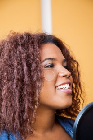 Woman With Curly Hair Singing In Recording Studio