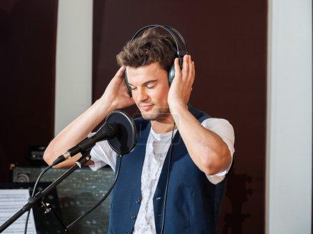 Photo pour Jeune chanteur écoutant attentivement de la musique à travers des écouteurs en studio d'enregistrement - image libre de droit