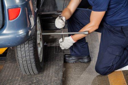 Mechanic Using Rim Wrench To Fix Tire