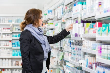 Female Purchaser Choosing Product At Pharmacy