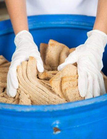 Womans Hands Discarding Bread Waste In Garbage Bin